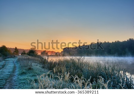 Autumn landscape - morning twilight over the lake. Fog over the water, the grass covered with frost - stock photo