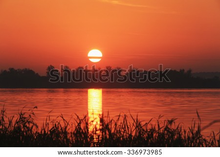 autumn landscape of bright red sunset over the river - stock photo
