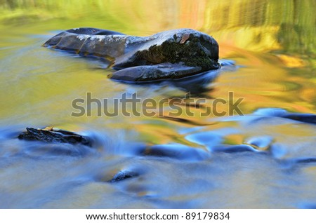 Autumn landscape of the Little River captured with motion blur and illuminated by reflected color from sunlit autumn foliage and blue sky overhead, Great Smoky Mountains National Park, Tennessee, USA - stock photo