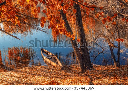 Autumn landscape of the river with the old wooden boat ashore. - stock photo