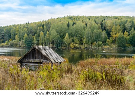 Autumn landscape. Old abandoned village on the empty field. Deteriorated typical ancient wooden abandoned house at village. Destroyed abandoned house standing in the forest. Belarus, Europe - stock photo
