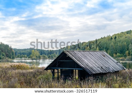 Autumn landscape. Old abandoned village on the empty field. Deteriorated typical ancient wooden abandoned house at village. Destroyed abandoned house standing in the forest. Belarus, Europe