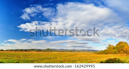 Autumn landscape with beautiful clouds and bright blue sky with golden fields  - stock photo