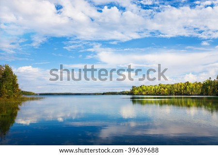 Autumn landscape with  lake, autumn trees and blue sky reflection in the water. Kawartha lakes, Ontario. - stock photo