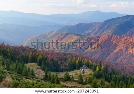 Autumn landscape with old wooden church in the mountains. Carpathians, Ukraine