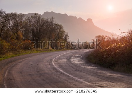 Autumn landscape with road. The gold light beams sunrise. On a background of mountains and the sky with clouds. - stock photo