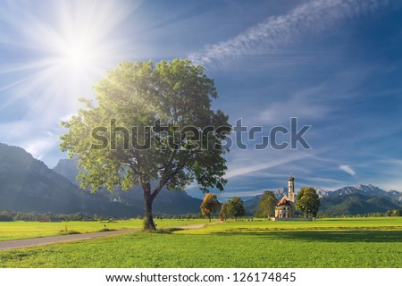 Autumn landscape with road, tree, church, mountains and sky on background - stock photo