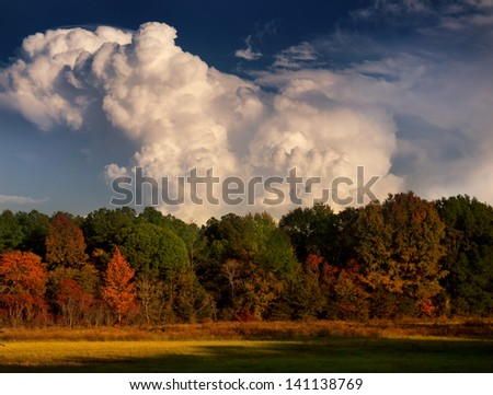 Autumn landscape with towering thunderheads. - stock photo