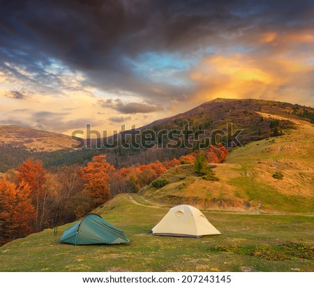 Autumn Landscape with two tents in the mountains. Beautiful night on the campsite - stock photo