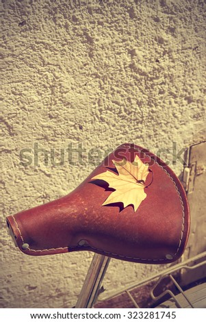 Autumn leaf over the saddle of an old bike. Vintage style. Concept arrival autumn. Vertical image.