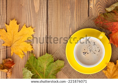 Autumn leaves and coffee cup over wood background with copy space - stock photo
