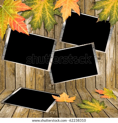 Autumn Leaves and photo frame over wooden background - stock photo