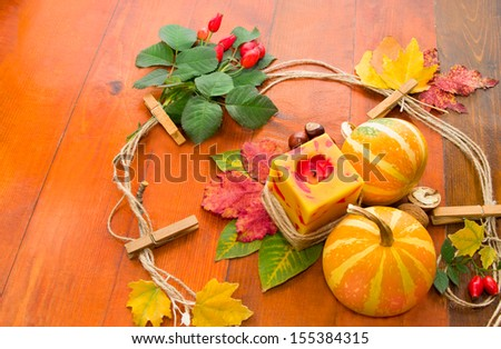 Autumn leaves and pumpkins. Composition on wooden background (pumpkin, candle, leaves, nuts, rose)