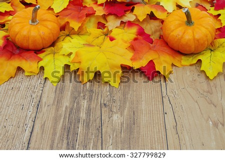 Autumn Leaves and Pumpkins on a Weathered Wood Background with space for your message