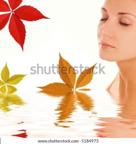 Autumn leaves around beautiful girl's face - stock photo