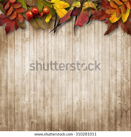 Autumn leaves border on vintage wooden background - stock photo