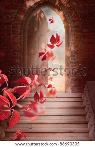Autumn leaves fall through the open door. - stock photo