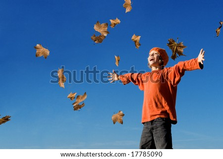 autumn leaves falling on boy - stock photo
