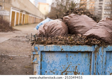 Autumn leaves in a garbage can - stock photo