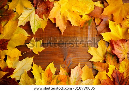 Autumn leaves over old wooden background. With copy space - stock photo