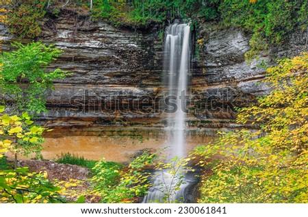Autumn leaves surround the beautiful Munising Falls, a waterfall in Upper Peninsula Michigan's Pictured Rocks National Lakeshore. - stock photo