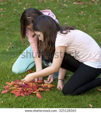 Autumn Leaves.Two girls are busily creating a sun out of brilliant red autumn leaves. - stock photo