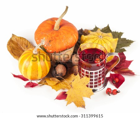 Autumn leaves with pumpkin, cup of tea with hip roses  - stock photo