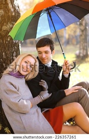 Autumn, love, relationships and people concept - lovely young couple with colorful umbrella in the park - stock photo