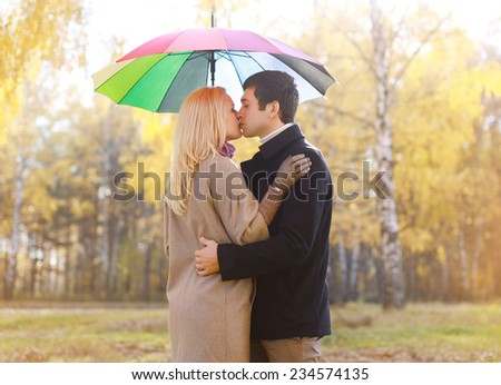 Autumn, love, relationships and people concept - sensual pretty couple in love outdoors with colorful umbrella  - stock photo