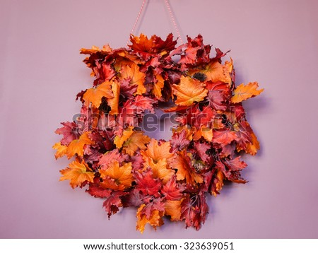 Autumn maple leaves in circle on the purple wall