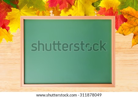 Autumn maple leaves over wood texture and school blackboard close-up - stock photo