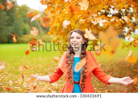 Autumn model, bright make up. woman on background fall landscape leaves of trees. Girl Model on autumn season. Fashion people. Girl throws autumn leaves