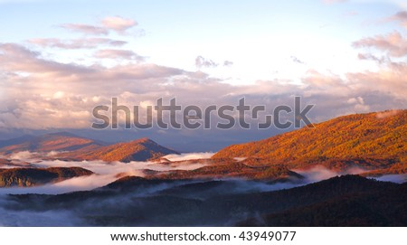Autumn morning mountain view with fog nestled in the mountain valleys. - stock photo