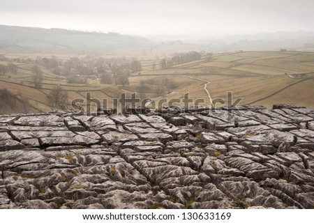 Autumn morning over limestone pavement at Malham Cove looking along Malham Dale in Yorkshire Dales National Park - stock photo