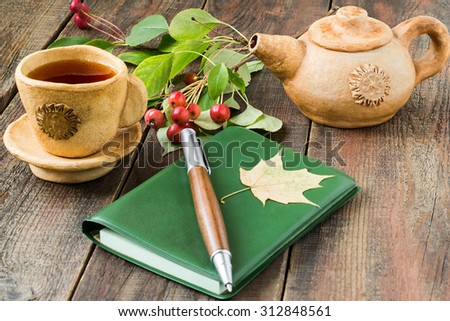 Autumn morning: tea in a clay cup and teapot, a sprig of chinese apples, diary and pen on the wooden table. Selective focus on tea - stock photo