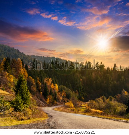 autumn mountain landscape. asphalt road going to mountains passes through the ever green coniferous shaded forest at sunset - stock photo
