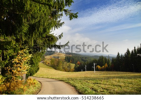 Autumn mountain landscape with blue sky and small clouds. Road through a meadow - Moravian-Silesian Beskydy