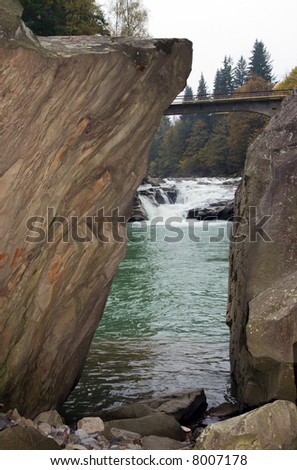 Autumn mountain river view through chink between two big rocks (with waterfall and bridge)