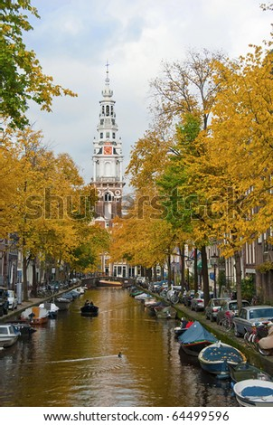 Autumn on a canal in Amsterdam with clock tower in background - stock photo