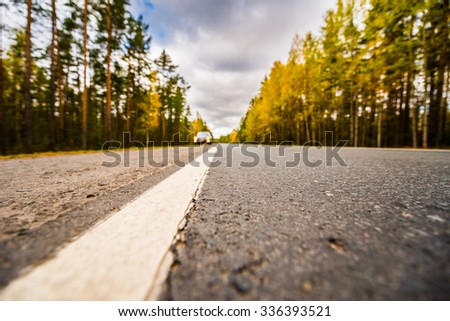 Autumn on the country road, the lights of the approaching car. View from the level of asphalt - stock photo