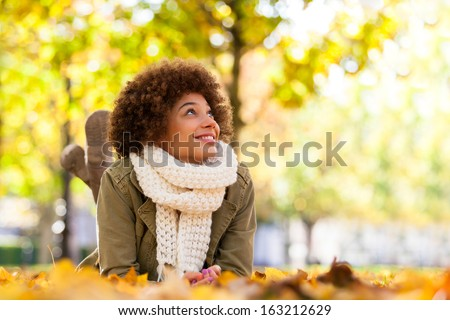 Autumn outdoor portrait of beautiful African American young woman lying down - Black people - stock photo