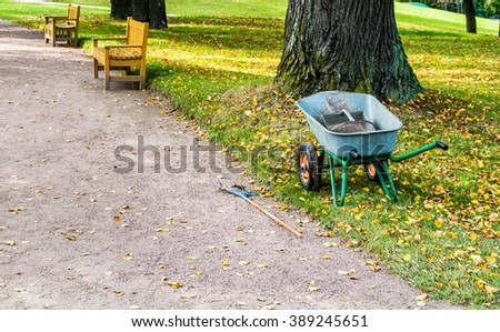 Autumn Park. Wheelbarrow for cleaning leaves standing near the road. - stock photo