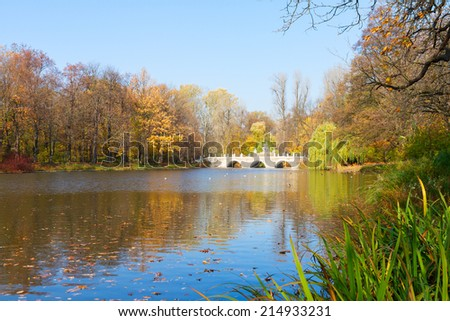 autumn park with trees over blue lake waters, Lazienki, Warsaw, Poland
