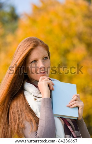 Autumn park - young red hair woman with book relax