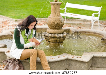 Autumn park young woman reading book sitting on fountain - stock photo