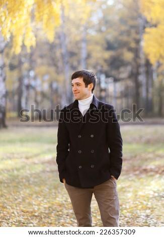 Autumn portrait handsome man in black coat outdoors  - stock photo