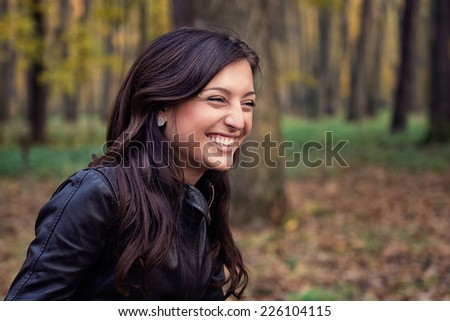 Autumn portrait of a beautiful cheerful woman. - stock photo