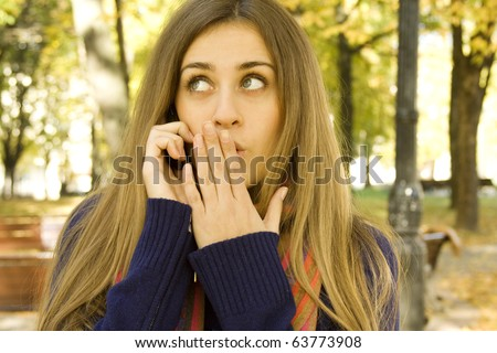 Autumn portrait of a beautiful girl outside on the phone shocking news - stock photo