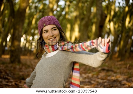 Autumn portrait of a beautiful happy young woman with a colored scarf