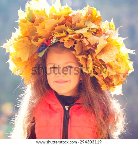 Autumn portrait of a little girl wearing a crown of yellow leaves. - stock photo